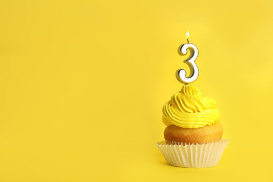 Birthday cupcake with number three candle on yellow background, space for text