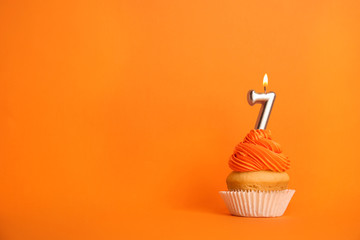 Birthday cupcake with number seven candle on orange background, space for text