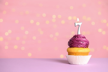 Birthday cupcake with number seven candle on table against festive lights, space for text