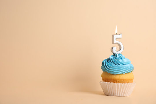 Birthday cupcake with number five candle on beige background, space for text