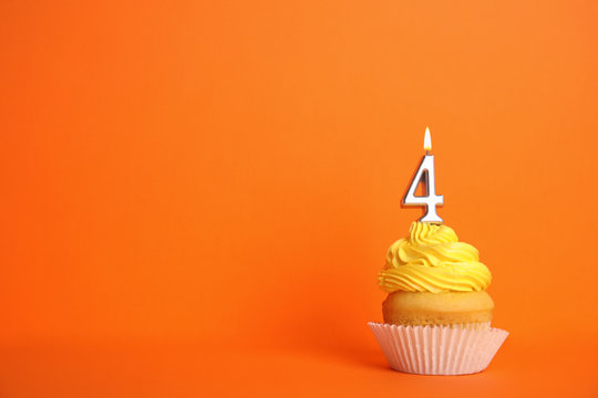 Birthday cupcake with number four candle on orange background, space for text
