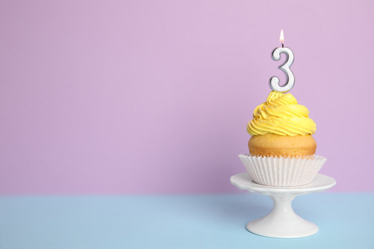 Birthday cupcake with number three candle on stand against color background, space for text