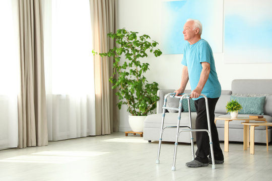 Elderly man using walking frame indoors. Space for text