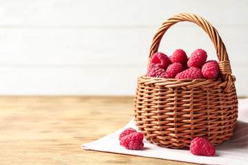Wicker basket with delicious ripe raspberries on wooden table against light background, space for text Fototapete