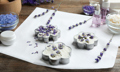 Handmade soap bars with lavender flowers in metal forms and ingredients on brown wooden table