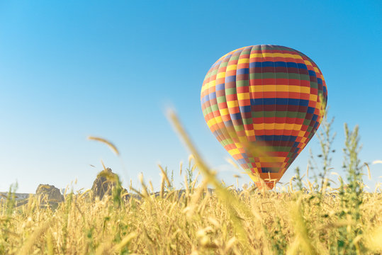 Multi-colored balloon flying in the sky in Cappadocia Turkey