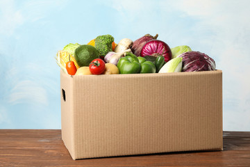 Fresh vegetables in cardboard box on wooden table
