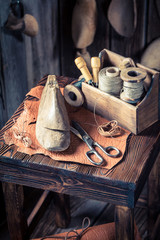 Closeup of shoelaces and tools in old shoemaker workplace