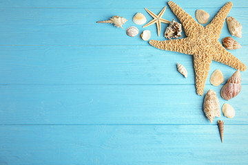 Flat lay composition with beautiful starfishes and sea shells on blue wooden table, space for text