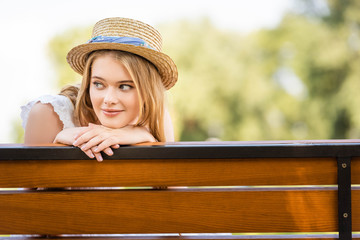 Wall Mural - beautiful girl in straw hat smiling while sitting on bench and looking away