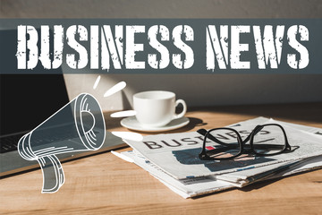 glasses on business newspaper near laptop and cup with saucer on wooden table with business news...