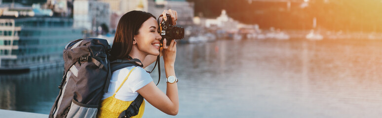 side view of asian woman with backpack taking photo
