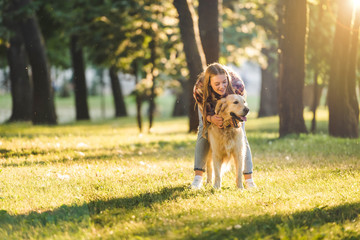 Wall Mural - full length view of beautiful girl in casual clothes hugging golden retriever while standing on meadow in sunlight