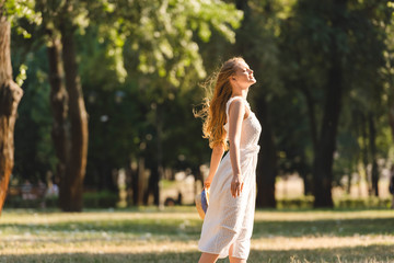 Wall Mural - side view of beautiful girl in white dress holding straw hat while smiling and standing on meadow with closed eyes