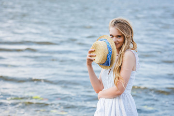 Wall Mural - beautiful girl holding straw hat near face, smiling and looking at camera