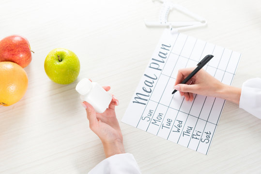 cropped view of dietitian holding pills and writing in meal plan at workplace