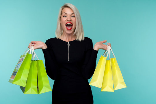 Young smiling woman holding shopping bags in black friday holiday. Happy Girl on blue background