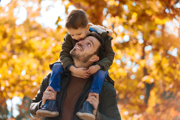 Happy father and little son playing and having fun outdoors over autumn park background