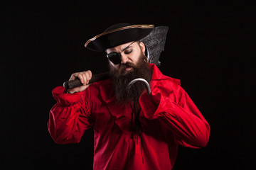 Thoughtful man in a pirate clothes for carnival with a hook insted of his hand