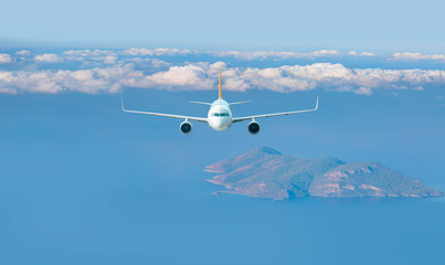 Airplane fly above beautiful island - White passenger airplane in the clouds - Travel by air transport