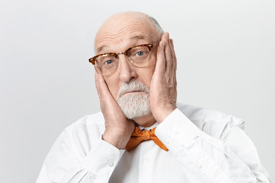 Funny bearded elderly man in stylish eyeglasses suffering from terrible toothache, holding hands on his cheeks, bugging out his blue eyes. Scared senior male expressing shock and astonishment