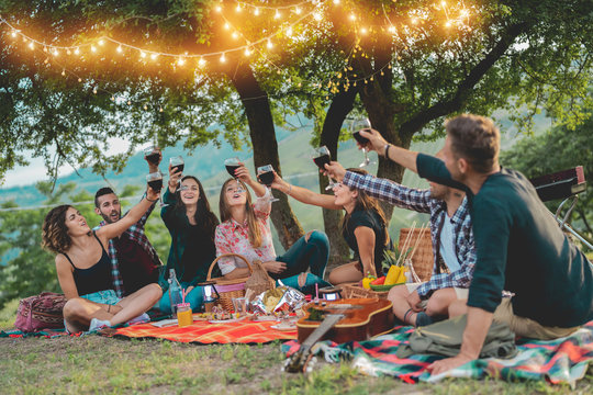 Happy friends having fun at picnic dinner with vintage lights outdoor next vineyard - Young people cheering with red wine on weekend summer night - Friendship, party concept - Focus on left guys faces