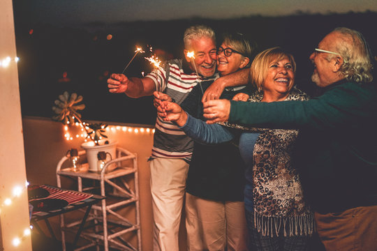 Group of senior friends celebrating birthday with sparkler fireworks on patio terrace - Happy people having fun after dinner in summer season  - Family and holidays concept - Focus on right woman face
