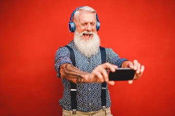 Senior hipster man using smartphone app for creating playlist with rock music - Trendy tattoo guy...