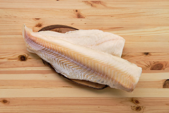 Frozen fillet of cod on wooden table