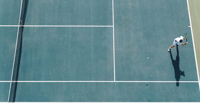 Tennis player hitting a backhand on hard court
