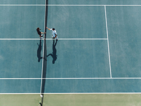 Tennis players shaking hands over the net