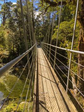 A narrow suspension footbridge spans across a river in New Zealand
