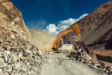 LADAKH, INDIA - SEPTEMBER 10, 2011: Tata Hitachi excavator cleaning road after landslide in Himalayas. Ladakh, Jammu and Kashmir, India