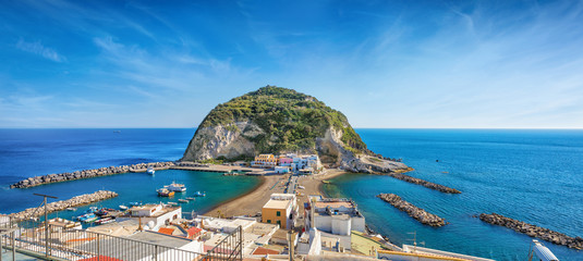 Panoramic view of beautiful coast of village Sant'Angelo, giant green rock in blue sea near Ischia Island, Italy.