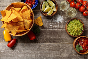 top view of Mexican nachos served with Tequila, guacamole and salsa on weathered wooden table