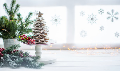 The handmade eatable gingerbread and New Year Tree with decoration. Gingerbread over defocused magic light winter window. Wonderful holiday mood. Copy space for your text.