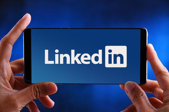 Hands holding smartphone displaying logo of LinkedIn