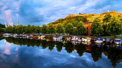 Wall Mural - Halden, Norway. View of the boats and yachts with Fredriksted fortress at the background. Time-lapse in the evening with cloudy sky in summer