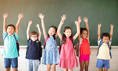 Group of diverse young students standing together in classroom