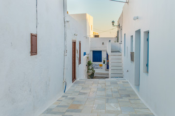 Street view of Plaka picturesque village with paved alleys and traditional houses in Milos island in Cyclades, Greece
