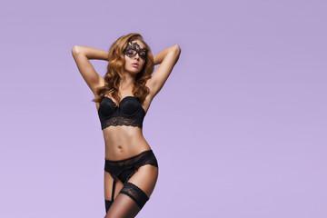 Fototapeta Fashion model posing in erotic underwear. Woman in beautiful black lingerie over colored background. obraz
