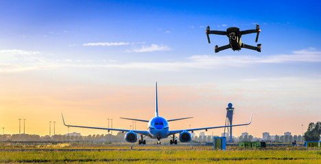 Unmanned drone flying near airplane at airport Wall mural