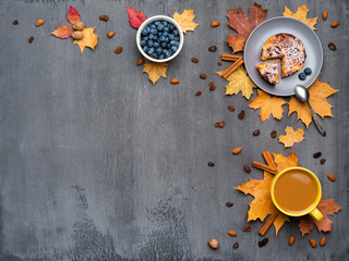 Wall Mural - Seasonal autumn background. Frame of colorful maple leaves and a cup of hot drink, coffee, latte or cappuccino, nutmeg, cake, blueberries and cinnamon over grey.