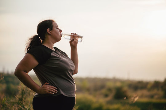 Overweight woman in sportswear drinking water after outdoor workout. Healthy lifestyle, hydration, weight loss, activity concept