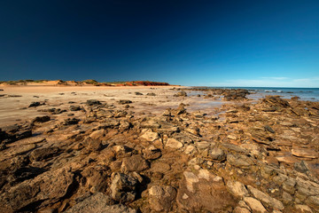 Western Australia - coast line at Dampier Peninsula with rocky shore, rippled sand dune and hill in the background in morning light