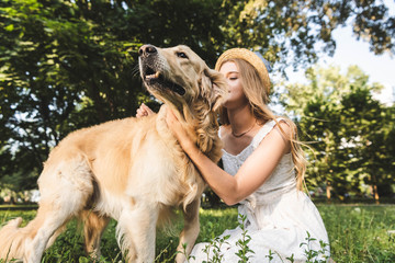 Wall Mural - beautiful girl in white dress and straw hat petting golden retriever