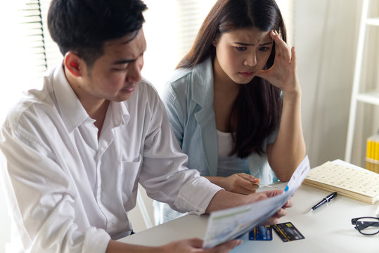 Stressed young Asian couples sitting with hands holding credit card and bills worry about find money to pay credit card debt and all loan bills. they are feeling stressful. Financial problem concept.