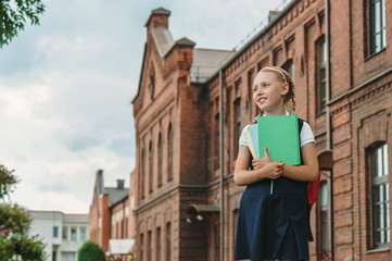 Portrait of schoolgirls with books in their hands. Against the background of an old building. Back to school concept.