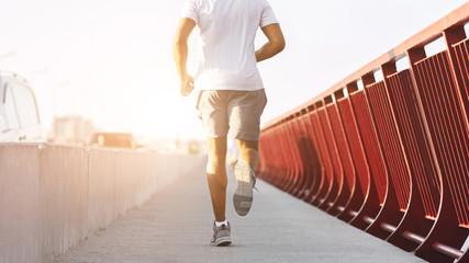 Cropped image of sporty afro man running on bridge