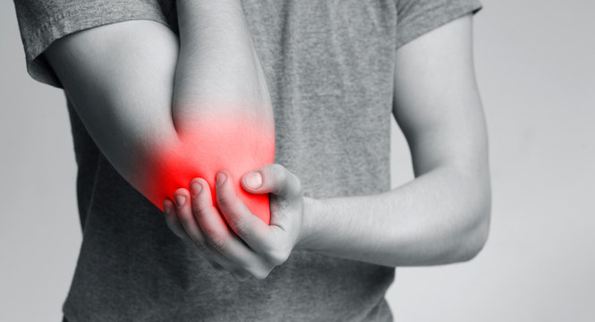 Young man suffering from pain in his elbow